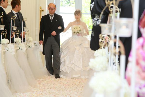 見渡す限り真っ白なチャペルでの挙式。花びらの敷かれたバージンロードを、最愛のお父様と…
