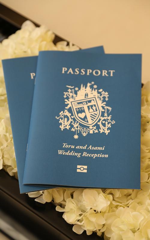 パスポートをモチーフにした席次表。席次表の裏には出国スタンプを押せるようにし、<br /> ゲスト全員と話せるようにようにしました。